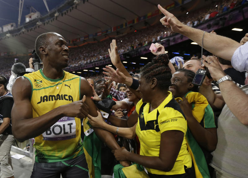 Jamaica's Usain Bolt, left, celebrates winning the gold medal in the men's 200-meter final during the athletics in the Olympic Stadium at the 2012 Summer Olympics, London, Thursday, Aug. 9, 2012. (AP Photo/Matt Rourke)