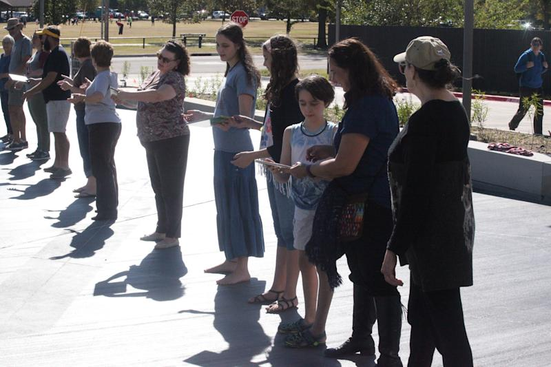 People in Norman, Oklahoma formed a human chain to deliver 100 library books to a new location. (Photo Credit: Christian Potts)
