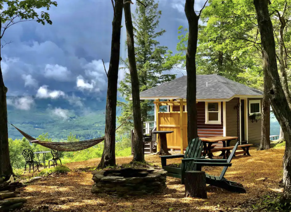 """<p><strong><a href=""""https://www.airbnb.com/rooms/43665674"""" rel=""""nofollow noopener"""" target=""""_blank"""" data-ylk=""""slk:Mahican Cabin"""" class=""""link rapid-noclick-resp"""">Mahican Cabin</a>: North Adams, Massachusetts</strong></p><p>This cute tiny house is in a perfect spot: it's on the highest peak of the Hoosac Range, super private, and offers amazing views. Plus, there are all the creature comforts included: air conditioning, heat, a nice deck, a grill, and a bathroom. The hammock and fire pit make it easy to spend tons of time outdoors, and there's even a concierge service that can set up your firepit and stock it with wood so you don't have to lift a finger.</p>"""