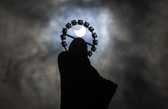 A statue of Our Lady, Star Of The Sea on Bull Wall in Dublin, is silhouetted against the sky during a partial solar eclipse, Thursday, June 10, 2021. (Brian Lawless/PA via AP)