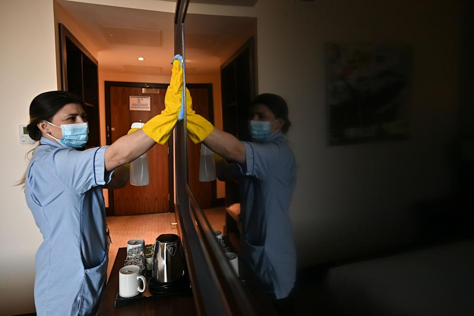 A member of the cleaning staff cleans surfaces as she prepares a room for a guest at the St Giles Hotel, near Heathrow Airport in west London, on February 10, 2021. - The Hotel has offered to become one of England's designated Covid-19 quarantine hotels. Health Secretary Matt Hancock told parliament that British or Irish residents arriving from 33 countries deemed high risk of new variants will have to stay in one of 16 designated hotels in England. Travellers will have to stay in their rooms, have meals delivered to them and pay out their own pocket. (Photo by Ben STANSALL / AFP) (Photo by BEN STANSALL/AFP via Getty Images)
