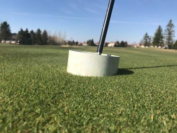 To reduce the number of surfaces people touch at golf courses in 2020, flags had to remain in place and cups are elevated,so the ball does not drop into the hole.
