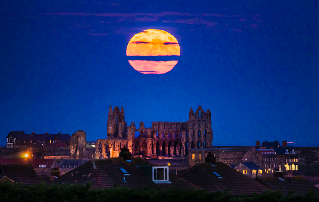 <p>A stern emoji face can be seen as clouds pass the moon above Whitby Abbey in Yorkshire. (PA) </p>