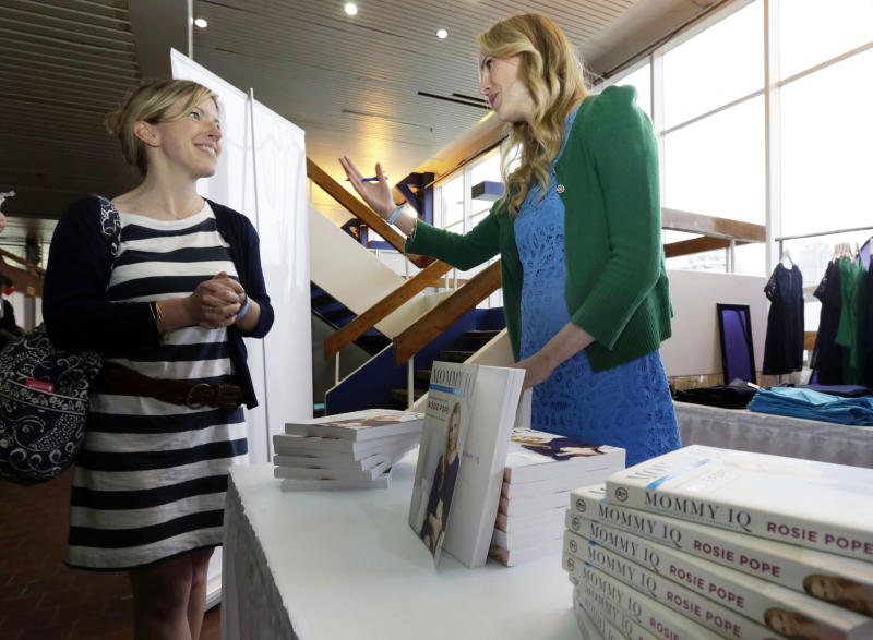 """This May 18, 2013 photo shows pregnancy advise guru Rosie Pope, center, speaks with an attendee at the New York Baby Show in New York. Pope is the author of the pregnancy guide, """"Mommy IQ,"""" and also has her own maternity clothing line. (AP Photo/Richard Drew, file)"""