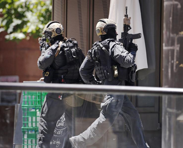 A police officer runs across Martin Place near Lindt cafe, where hostages are being held, in central Sydney December 15, 2014. Hostages were being held inside the central Sydney cafe where a black flag with white Arabic writing could be seen in the window, local television showed on Monday, raising fears of an attack linked to Islamic militants.      REUTERS/David Gray (AUSTRALIA - Tags: CRIME LAW CIVIL UNREST)