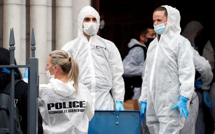 Forensic police officers inspect the scene of a knife attack at Notre Dame church in Nice - Eric Gaillard/Pool Reuters