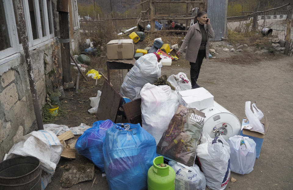 A woman speaks on the phone next to her possessions, as she prepares to leave an area once occupied by Armenian forces but soon to be turned over to Azerbaijan, in Yekhetnut, the separatist region of Nagorno-Karabakh, on Friday, Nov. 13, 2020. Under an agreement ending weeks of intense fighting over the Nagorno-Karabakh region, some Armenian-held territories adjacent to the region are passing to Azerbaijan. (AP Photo/Dmitry Lovetsky)