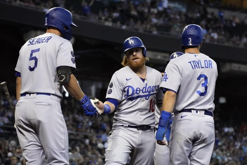 Los Angeles Dodgers' Justin Turner celebrates with Corey Seager (5) and Chris Taylor (3) after scoring runs on a double hit by Albert Pujols in the second inning of a baseball game against the Arizona Diamondbacks, Sunday, Aug 1, 2021, in Phoenix. (AP Photo/Rick Scuteri)