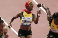 FILE - In this Friday, Oct. 4, 2019 file photo, Jamaica's Shelly-Ann Fraser-Pryce, center, hands off to Jonielle Smith, right, during a women's 4x100 meter relay semifinal at the World Athletics Championships in Doha, Qatar. On Friday, June 25, 2021, Fraser-Pryce cruised to a victory in the 100 meters at Jamaican national championships and will head to Tokyo in search of her third Olympic gold medal. (AP Photo/Nariman El-Mofty, File)