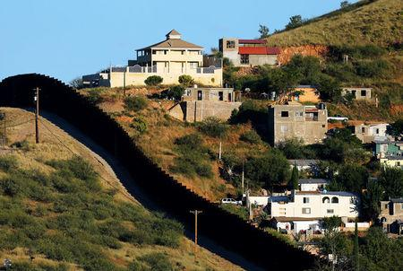FILE PHOTO: Buildings in Nogales, Mexico (R) are separated by a border fence from Nogales, Arizona, United Sates, October 9, 2016. REUTERS/Mike Blake/File Photo