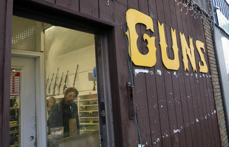 FILE - This Dec. 19, 2012 file photo show rifles line a wall above in front of people standing in a gun shop in Seattle. The slaying of five dozen people at a Las Vegas music festival did little to change American opinion about the nation's gun laws, and the country is divided over whether restricting firearms would reduce the number of such mass shootings or homicides, according to a new poll from The Associated Press-NORC Center for Public Affairs Research. (AP Photo/Elaine Thompson,File)