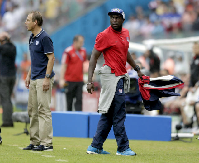 United States' Jozy Altidore walks back to the team bench after questioning a call on the pitch during the group G World Cup soccer match between the USA and Germany at the Arena Pernambuco in Recife, Brazil, Thursday, June 26, 2014. Left is United States' head coach Juergen Klinsmann. (AP Photo/Julio Cortez)