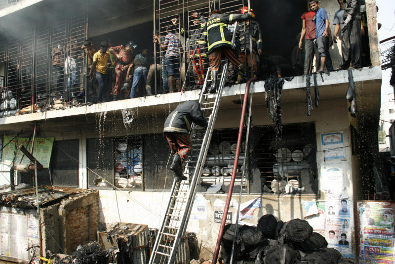 Bangladeshi firefighters and workers try to douse the fire at a garment-factory in Dhaka, Bangladesh, Monday, Nov. 26, 2012  two days after a similar incident killed more than 110 people on the outskirts. No casualty was reported in Monday's fire.   Bangladeshis were Monday blocking the streets near Dhaka, throwing stones at factories and smashing vehicles, as they demanded justice for those killed in Saturday's  fire.  (AP Photo)
