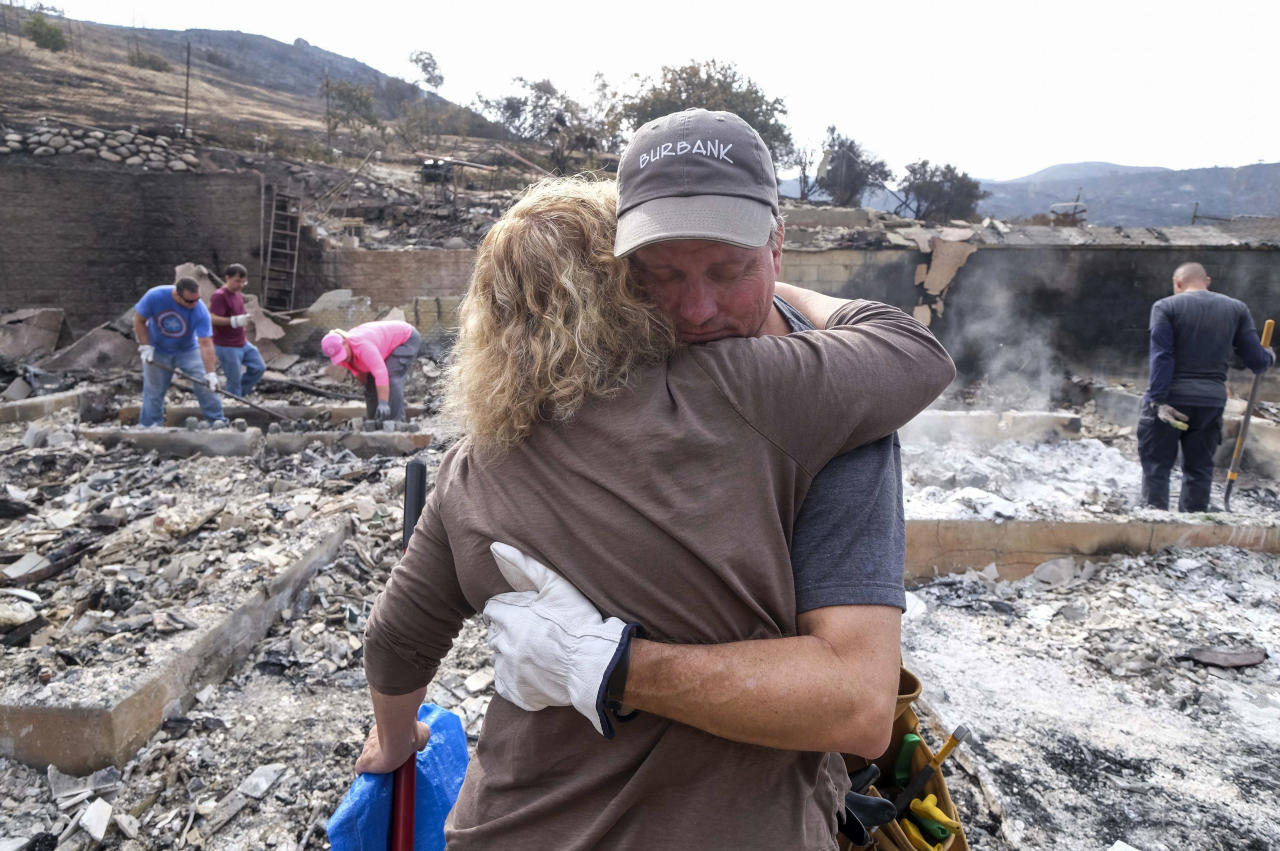 <p>Craig Bolleson hugs his friend in his burned out home, Monday, Sept. 4, 2017, in the Sunland-Tujunga section of Los Angeles. (Photo: Ringo H.W. Chiu/AP) </p>