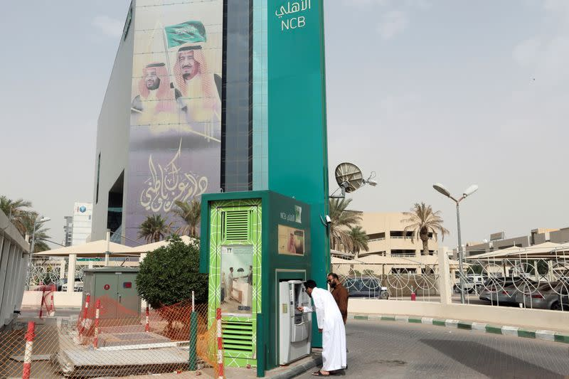 A man withdraws money from an ATM outside the Saudi NCB bank, after an outbreak of coronavirus, in Riyadh