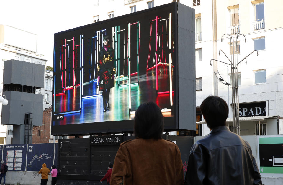 People watch a giant screen streaming a Fendi fashion live show during the Milan's fashion week in Milan, Italy, Friday, Jan. 15, 2021. (AP Photo/Antonio Calanni)