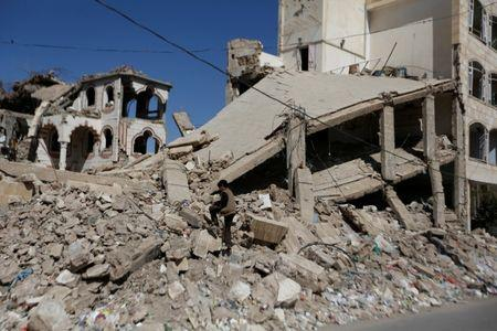 Boy walks on the wreckage of a building hit by air strikes two years ago in Sanaa