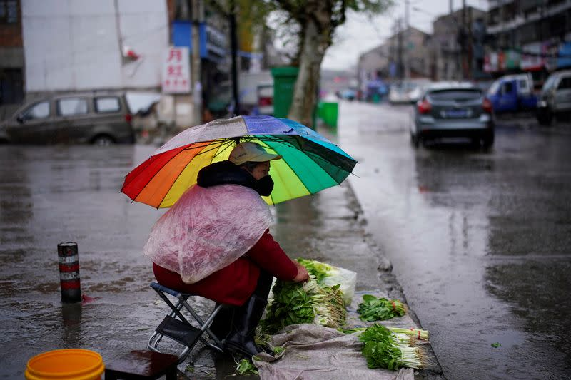 Vegetables vendor wearing a face mask waits for customers in the rain in Jingzhou