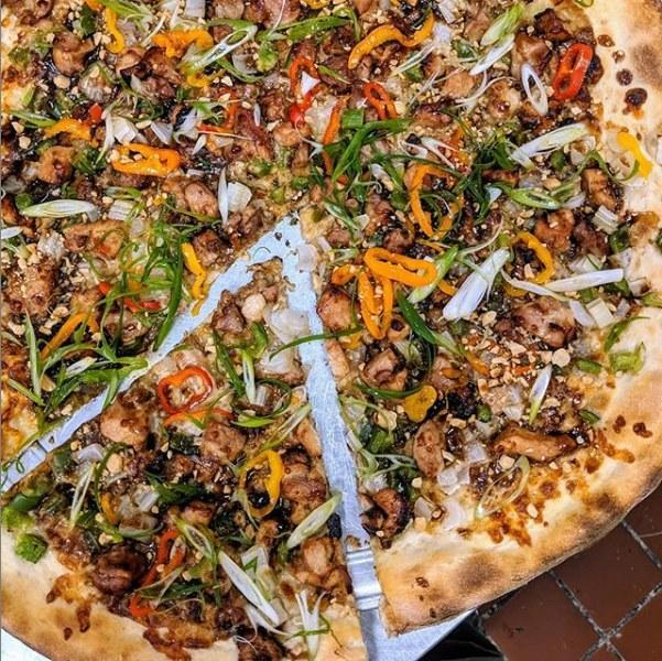 <p><strong>Tell us about your first impressions when you arrived.</strong><br> Dragon Pizza is a neo-retro place that takes inspiration from the super-casual, counter-service, by-the-slice joints that co-owner Charlie Redd grew up with in the 1980s and 1990s. Today's interpretation has a bit of an old-school, punk-rock sensibility, with cassettes lined up on the walls and menus scrawled in what looks like spray paint and Sharpie on sheets of poster board and paper plates. Aside from what comes in through the big plate-glass windows, lighting is fluorescent, and there are minimal seats and tables made from molded plywood.</p> <p><strong>What's the crowd like?</strong><br> The clientele, most of whom are there for take-out, given the 25 or so seats, is as diverse as the population of the neighborhood around Davis Square, one stop north of Harvard Square on the metro's Red Line. There are plenty of families, lots of students, young professionals, and older couples, plus pizza pilgrims from all over the city. (One of the <em>Boston Globe's</em> food writers called Dragon's pies the best pizza in town weeks after it opened, which brought in the pizza junkies.)</p> <p><strong>What should we be drinking?</strong><br> Dragon serves house-made sodas and coffee drinks. It's BYOB, but there's a liquor store across the street.</p> <p><strong>Main event: the pizza. Give us the lowdown—especially what not to miss.</strong><br> Much like the atmosphere, the pizza is similarly old-school: big, New York–style thin-crust pies topped with a mix of classic Italian cheeses and simple tomato sauce. They're also made with high-quality ingredients; the raw materials for the red sauce, for example, come from a favorite family-run tomato company in California. But old school doesn't mean there isn't room for experimentation; peppered among the standard pies—margherita, peperoni—are signature combos like maple bacon and cheddar, and Kung Pao chicken. Between those two poles are offerings like