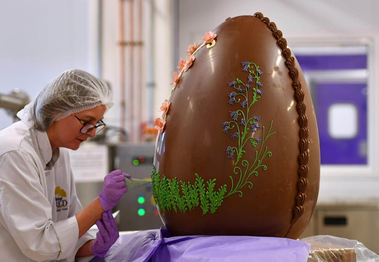 <p>Chocolatier Dawn Jenks decorates a giant chocolate egg at Cadbury World in Birmingham. (PA) </p>