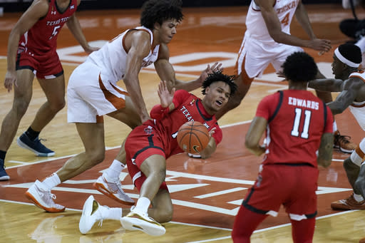 Texas Tech guard Terrence Shannon Jr. (1) passes the ball away from Texas forward Jericho Sims (20) as he loses his balance during the second half of an NCAA college basketball game Wednesday, Jan. 13, 2021, in Austin, Texas. (AP Photo/Eric Gay)