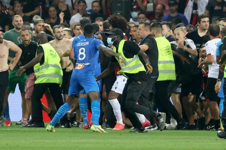 Flash point: Security try to hold back fans as they invade the pitch at Nice's Allianz Riviera Stadium
