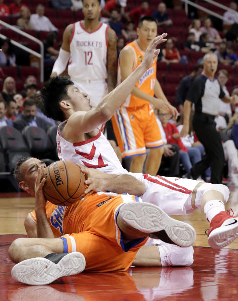 Shanghai Sharks forward Luis Scola (4) comes up with the ball as Houston Rockets forward Zhou Qi (9) reacts in pain after injuring his left knee during the loose ball scramble play during the first half of an exhibition NBA basketball game Tuesday, Oct. 9, 2018, in Houston. Qi was taken off the court in a wheelchair. (AP Photo/Michael Wyke)