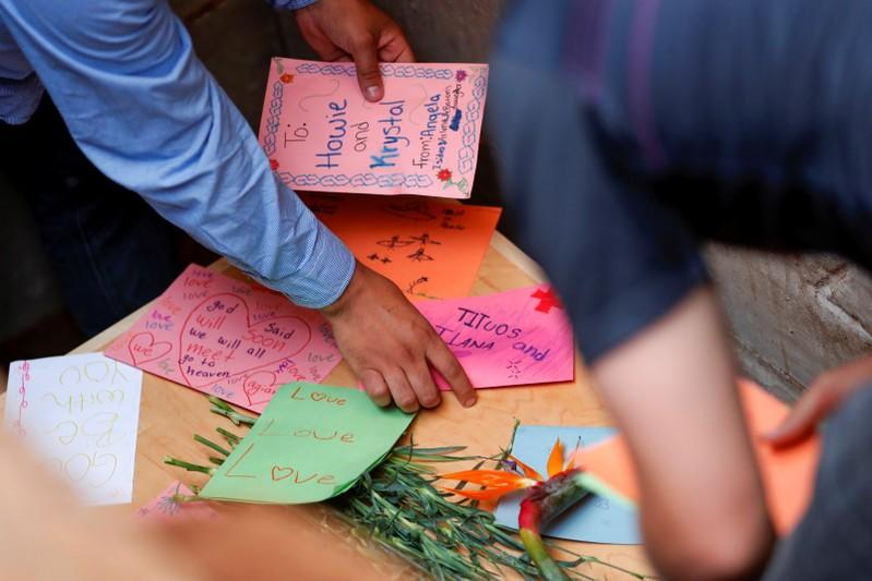 Relatives put cards on top of one of the coffins during the burial of Rhonita Miller and her children Howard, Kristal, Titus, and Teana, who were killed by unknown assailants, in LeBaron