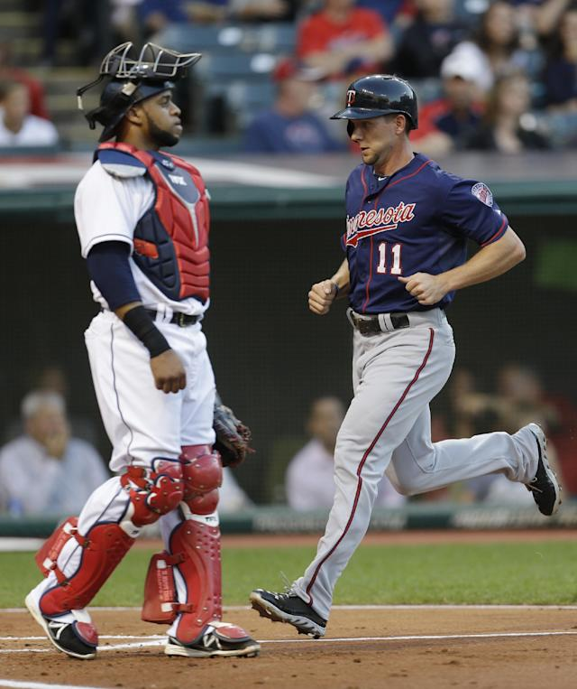 Minnesota Twins' Clete Thomas, right, scores as Cleveland Indians catcher Carlos Santana watches in the second inning of a baseball game on Friday, Aug. 23, 2013, in Cleveland. Thomas scored on an RBI-double by Pedro Florimon. (AP Photo/Tony Dejak)