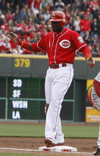Cincinnati Reds' Brandon Phillips tag third base after hitting an RBI-triple off Houston Astros pitcher Lucas Harrell during the first inning of a baseball game on Saturday, April 28, 2012, in Cincinnati. (AP Photo/David Kohl)