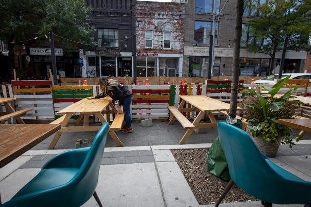 A restaurant employee cleans a table set up in the curb lane at a Toronto restaurant last September. City officials confirmed the CaféTO program that helped hundreds of restaurant and bars expand patios into curb lanes and along sidewalks won't be up and running until early May this year.