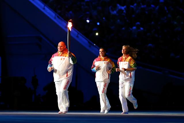 SOCHI, RUSSIA - FEBRUARY 07: Alexandr Karelin (L) carries the Olympic torch as Elena Isinbaeva (C) and Maria Sharapova follow during the Opening Ceremony of the Sochi 2014 Winter Olympics at Fisht Olympic Stadium on February 7, 2014 in Sochi, Russia. (Photo by Ryan Pierse/Getty Images)