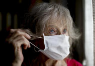 Carmela Corleto adjusts her mask as she peers out the window of her home where she lives alone and waits her turn to get a COVID-19 vaccine in Burzaco, Argentina, Thursday, Feb. 18, 2021. Corleto, who said she never imagined the lockdown would last so long, or that COVID-19 would be so contagious and dangerous, got her first shot of the AstraZeneca vaccine on April 23, 2021. (AP Photo/Natacha Pisarenko)