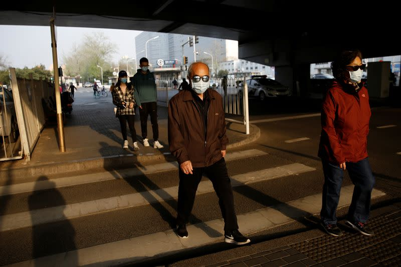 People wearing protective face masks walk across a street in Beijing, as the spread of the novel coronavirus disease (COVID-19) continues in the country