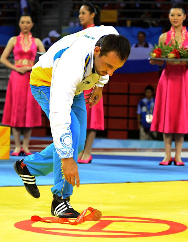 """** FILE ** In this Aug. 14, 2008 file photo, Swedish wrestler Ara Abrahamian leaves his medal on the mat during the medal ceremony in protest at the Beijing 2008 Olympics in Beijing. Abrahamian was banned for two years along with his coach for """"scandalous behavior,"""" the sport's governing body said Thursday Nov. 6, 2008. (AP Photo/Vanda Biffani, File) ** NO SALES **"""