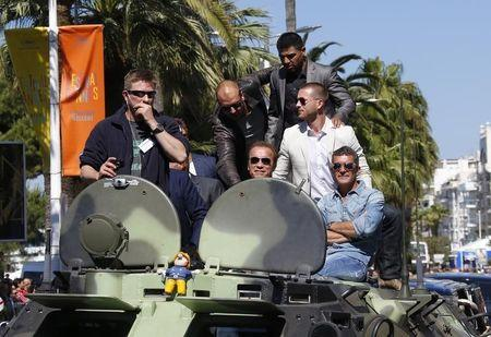 "Cast members Randy Couture, Arnold Schwarzenegger, Victor Ortiz, Glen Powell and Antonio Banderas pose on a tank as they arrive on the Croisette to promote the film ""The Expendables 3"" during the 67th Cannes Film Festival in Cannes"