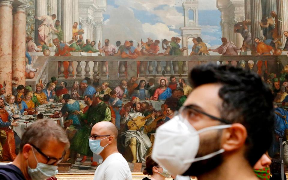 """Visitors wearing face mask stands in front of """"The Wedding Feast at Cana"""" oil on canvas painting by the Italian artist Paolo Veronese - AFP"""