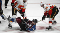 Colorado Avalanche left wing Gabriel Landeskog, center, falls on the puck, next to Calgary Flames defenseman Noah Hanifin, left, and center Elias Lindholm in overtime of Game 4 of an NHL hockey playoff series Wednesday, April 17, 2019, in Denver. The Avalanche won 3-2. (AP Photo/David Zalubowski)
