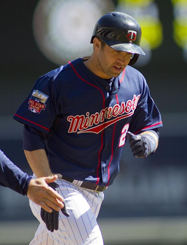 Minnesota Twins second baseman Brian Dozier (2) is congratulated after hitting a home run against Oakland Athletics in the first inning of their baseball game on Thursday, April 10, 2014 in Minneapolis.(AP Photo/Andy Clayton-King)