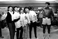 <p>In this Feb. 18, 1964, file photo, The Beatles, from left, Paul McCartney, John Lennon, Ringo Starr, and George Harrison, take a fake blow from Cassius Clay, who later changed his name to Muhammad Ali, while visiting the heavyweight contender at his training camp in Miami Beach, Fla. Ali turns 70 on Jan. 17, 2012. (AP Photo/File)</p>