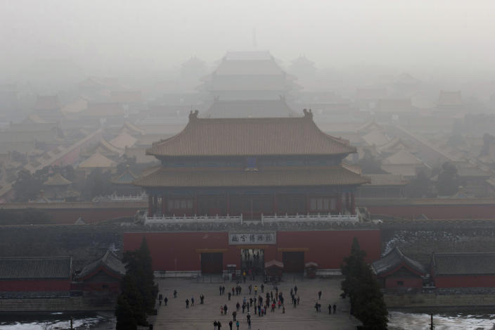 FILE - In this Jan. 13, 2013 file photo, visitors gather near an entrance to the Forbidden city during a very hazy day in Beijing. China, one of the most visited countries in the world, has seen sharply fewer tourists this year, with worsening air pollution partly to blame. (AP Photo/Ng Han Guan, File)
