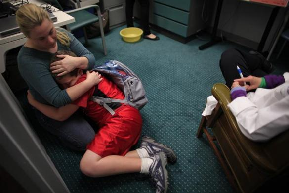 Parker Roos, who suffers from Fragile X, is comforted by his mother Holly during a check up at the Fragile X Clinic and Research Program at Rush University Medical Center in Chicago, April 11, 2012.