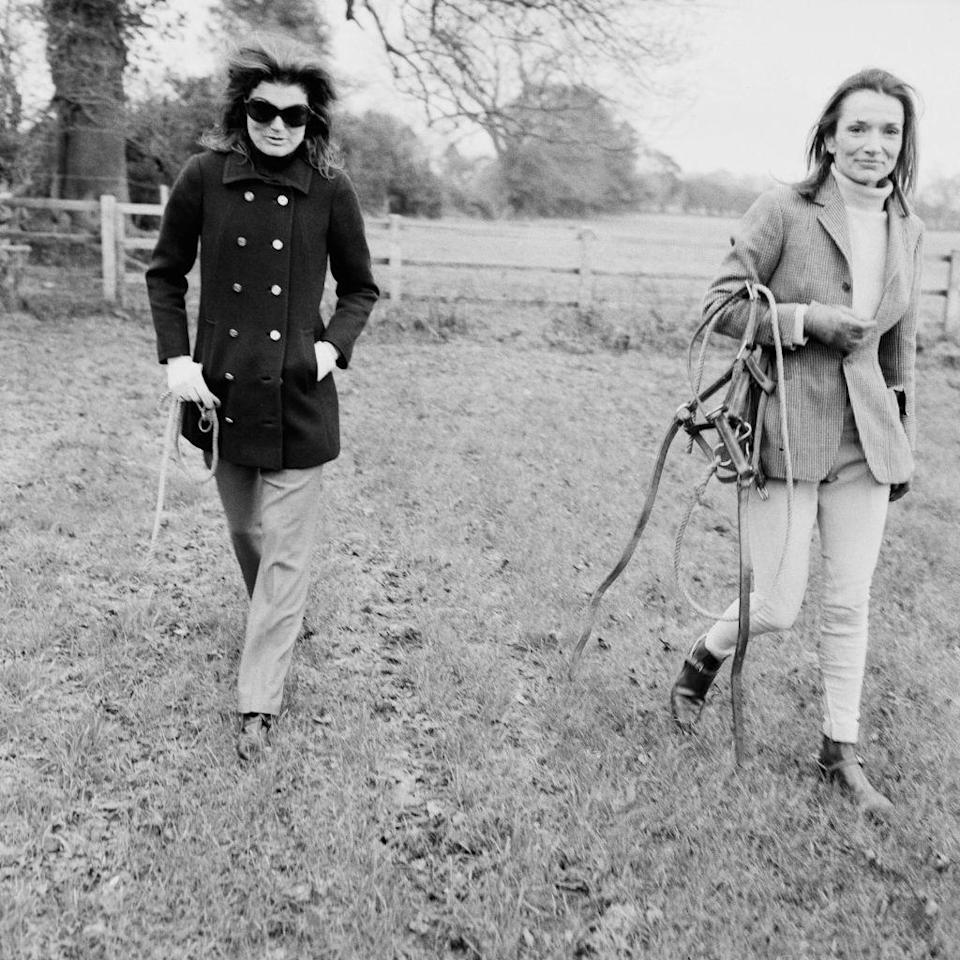 <p>Jackie and Lee Radziwill are photographed at a horse farm in the United Kingdom, appropriately dress in wool and tweed.<br></p>