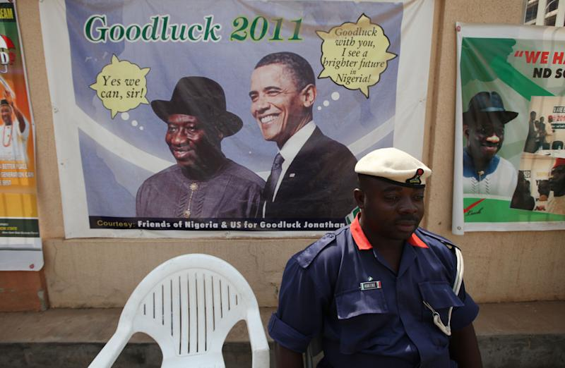 A Nigerian security man sits under a campaign poster  of, Nigeria President Goodluck Jonathan, with US President Barrack Obama, in Abuja, Nigeria, Wednesday, Jan. 12, 2011. Nigeria's ruling political party will pick its presidential candidate Thursday for the coming April election, a decision that might be made based on where the candidate is from rather than what he has to offer.  That vote, pitting President Goodluck Jonathan against former Vice President Atiku Abubakar, highlights the religious and ethnic fault lines still running through the oil-rich nation of 250 ethnicities more than 40 years after its deadly civil war. (AP Photo/Sunday Alamba)