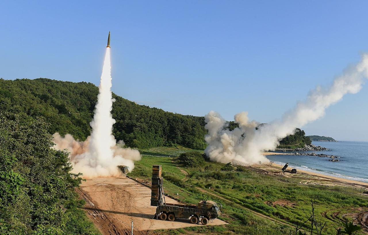 <p>South Korea's Hyunmu-2 Missile System (L) and U.S. M270 Multiple Launch Rocket System (R) firing missiles during a U.S. and South Korea joint missile drill aimed to counter North Korea's intercontinental ballistic missile test on July 5, 2017 in East Coast, South Korea. The U.S. Army and South Korean military responded to North Korea's missile launch with a combined ballistic missile exercise on Wednesday, into South Korean waters along the country's eastern coastline. (Photo: South Korean Defense Ministry via Getty Images) </p>