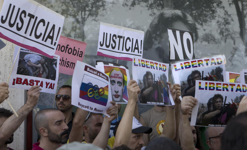 """Gay rights protesters hold up posters during a protest in front of the Russian embassy in Madrid, Spain Friday Aug. 23, 2013 against Russia's new law on gays. Protesters, called for the Winter 2014 Olympic Games to be taken away from Sochi, Russia, because of a new Russian law that bans """"propaganda of nontraditional sexual relations"""" and imposes fines on those holding gay pride rallies. Posters read ' Justice, Freedom, That's enough, Boycott Russia and Stop Homophobia'. (AP Photo/Paul White)"""