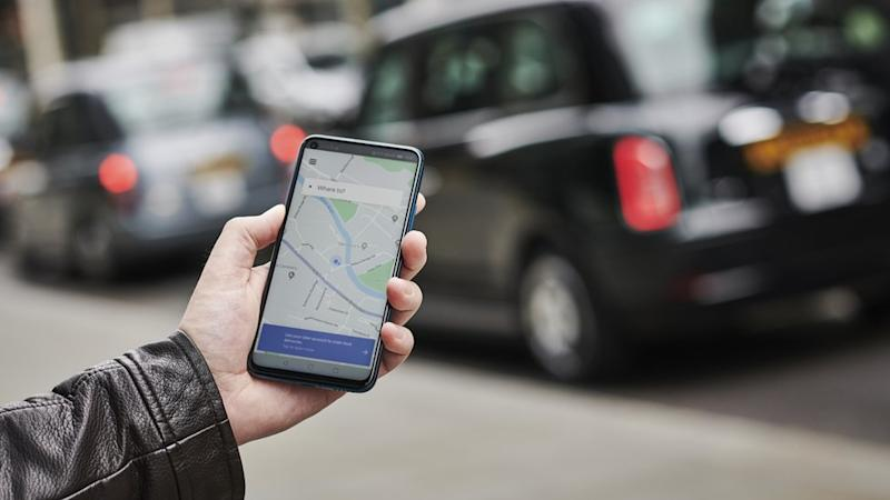 a man with the Uber app open on his smart phone