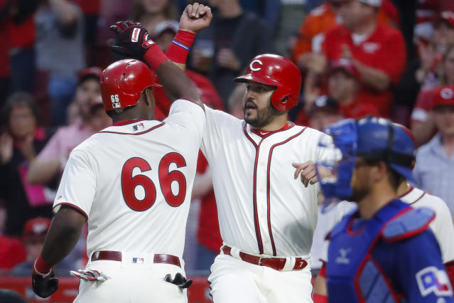 Cincinnati Reds' Yasiel Puig (66) celebrates with Eugenio Suarez, center, after hitting a two-run home run off Texas Rangers starting pitcher Mike Minor during the fourth inning of a baseball game Saturday, June 15, 2019, in Cincinnati. (AP Photo/John Minchillo)