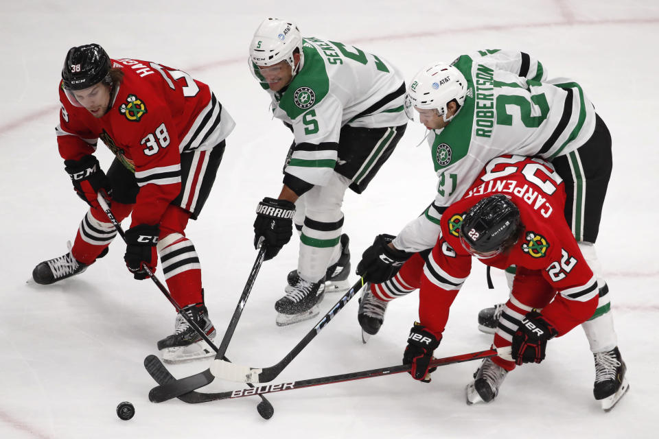 Chicago Blackhawks left wing Brandon Hagel (38) and teammate Ryan Carpenter (22) battle for the puck with Dallas Stars defenseman Andrej Sekera (5) and left wing Jason Robertson (21) during the second period of an NHL hockey game Tuesday, April 6, 2021, in Chicago. (AP Photo/Jeff Haynes)
