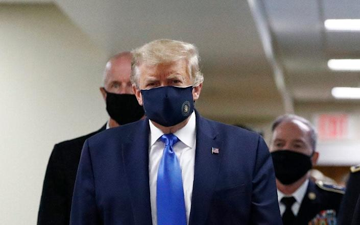 President Donald Trump, foreground left, wears a face mask as he walks with others down a hallway during a visit to Walter Reed National Military Medical Center in Bethesda - patrick Semansky / AP